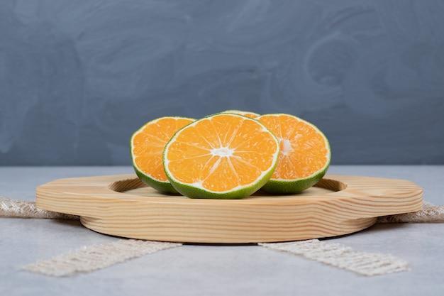 Кусочки свежих мандаринов на деревянной тарелке.