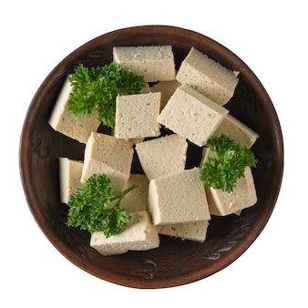 Кусочки свежего сыра тофу в глиняной миске, изолированные на белой поверхности. соевый сыр. вегетарианский продукт. плоская планировка.