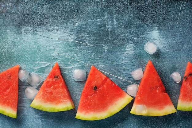 Кусочки свежего арбуза со льдом на синем бетонном столе. детокс и вегетарианская концепция. вид сверху, копия пространства, баннер