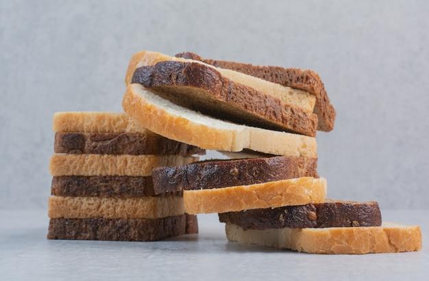Кусочки свежего белого и черного хлеба на мраморном фоне.