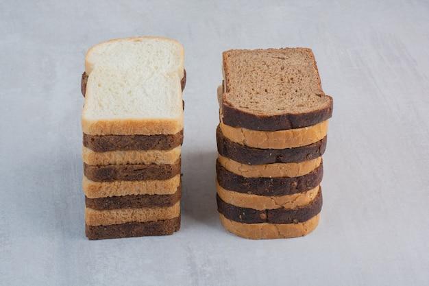 大理石の背景に焼きたての白と茶色のパンのスライス。
