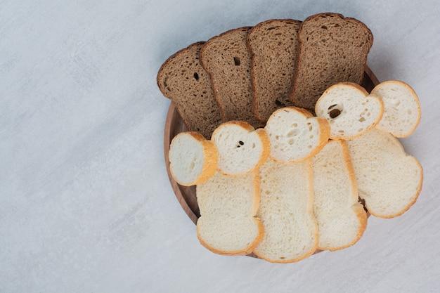 대리석 바탕에 신선한 흰색과 갈색 빵 조각. 무료 사진