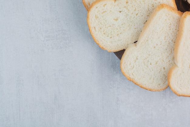 Кусочки свежего белого хлеба на мраморном фоне.