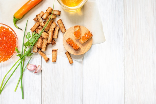 Ломтики жареных гренок со сметанным соусом, красным перцем, икрой и зубчиками чеснока на белых деревянных досках