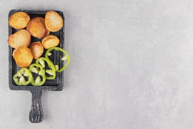 Кусочки жареного картофеля и перца на черной доске.