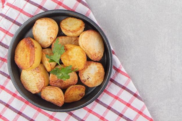 Кусочки жареного картофеля на черной тарелке.