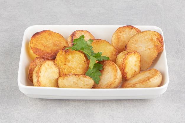 Кусочки жареного картофеля на белой тарелке.