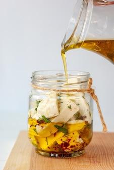 透明なガラスの瓶にオリーブオイルとグルジアのイメレティチーズのスライス