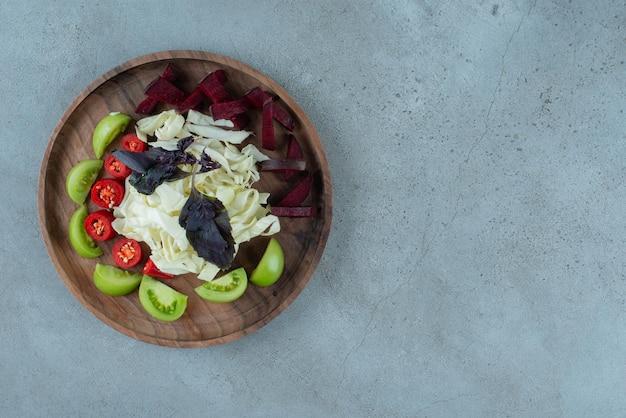 Ломтики зеленого помидора и нарезанной капусты на деревянной тарелке.