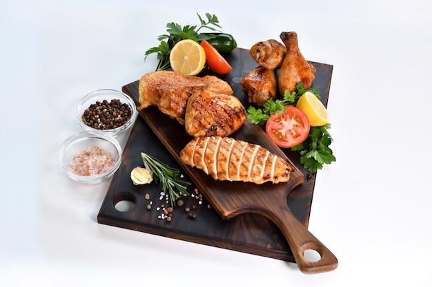 흰색 테이블에 나무 커팅 보드에 재료와 구운 닭 가슴살 조각