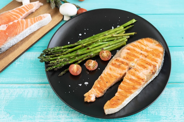 Ломтики жареного лосося с зеленой спаржей. скопируйте пространство.