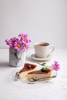 明るい背景にブルーベリーとミントの葉とプレート上の自家製バスク焼きチーズケーキのスライス
