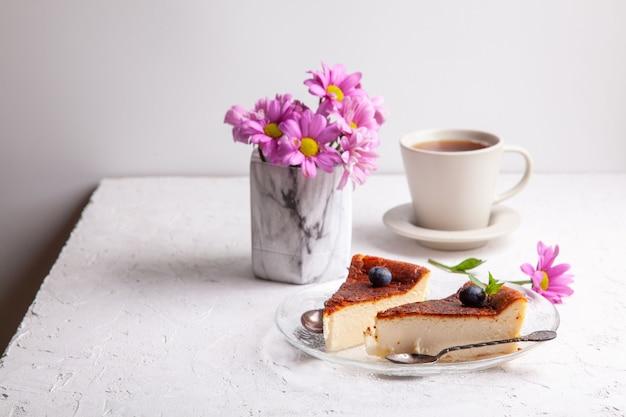 ブルーベリーとミントの葉とプレート上の自家製バスク焼きチーズケーキのスライス、花瓶の花と明るい背景の紅茶のカップ