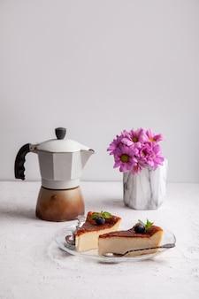 ブルーベリーとミントの葉、間欠泉コーヒーメーカー、花瓶の花と自家製バスク焼きチーズケーキのスライス