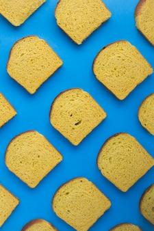 青い背景に自家製にんじんパンのスライス。場所は垂直です。上面図。フラットレイ。