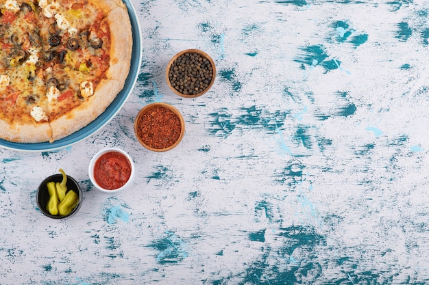大理石の背景に胡椒と胡椒の粉を添えたホットピザのスライス。
