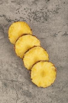 石の表面に置かれたジューシーでおいしいパイナップルのスライス。