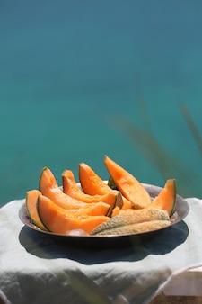 가벼운 천에 접시에 즙이 많은 오렌지 멜론 조각