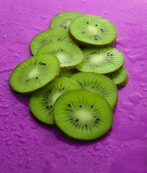 Ломтики киви в воде падает на фиолетовом фоне. фруктовая концепция.