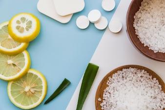 Slices of lemon; aloevera; sponge and rock salts on dual backdrop