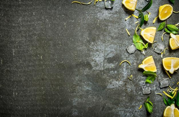 Ломтики лимона, льда, листьев на каменном столе. свободное место для текста. вид сверху