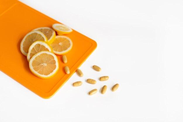 Дольки лимона лежат на разделочной доске. рядом находятся витамины с.