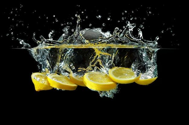 Ломтики лимона, брошенные в воду на черном фоне