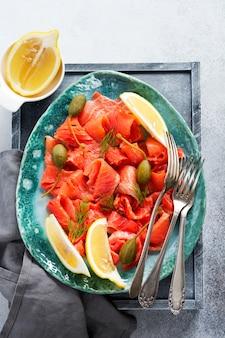 회색 콘크리트 배경의 세라믹 접시에 케이퍼, 레몬, 딜을 곁들인 가볍게 소금에 절인 연어 조각. 평면도
