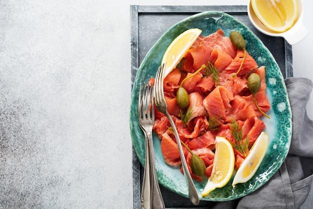Кусочки малосольного лосося с каперсами, лимоном и укропом на керамической тарелке на сером бетонном столе. вид сверху.