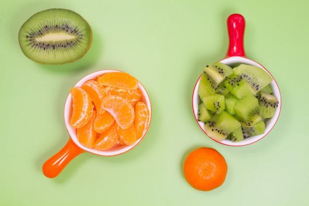 Ломтики мандариновой апельсиновой тарелки. ломтики киви в красной тарелке. половина киви и мандарина на зеленом фоне