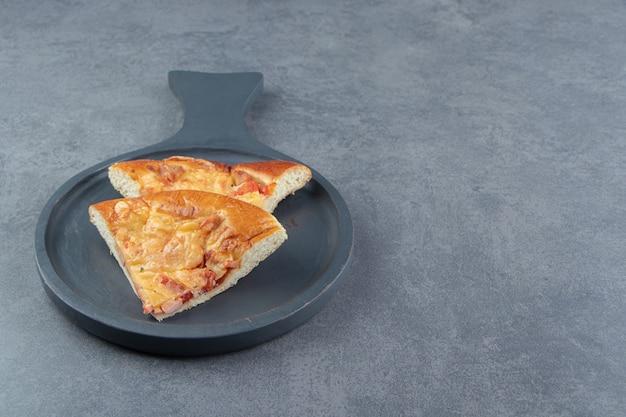黒のまな板にミックスピザのスライス。