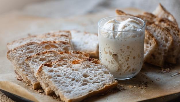 Ломтики натурального, домашнего хлеба без дрожжей и закваски в стакане