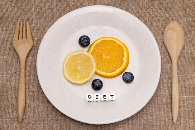 Дольки апельсина и лимона с черникой на белой керамической тарелке