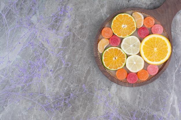 보드에 오렌지, 레몬, 귤, 사탕 조각.
