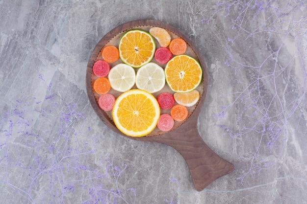 오렌지, 귤, 커팅 보드에 사탕의 조각.