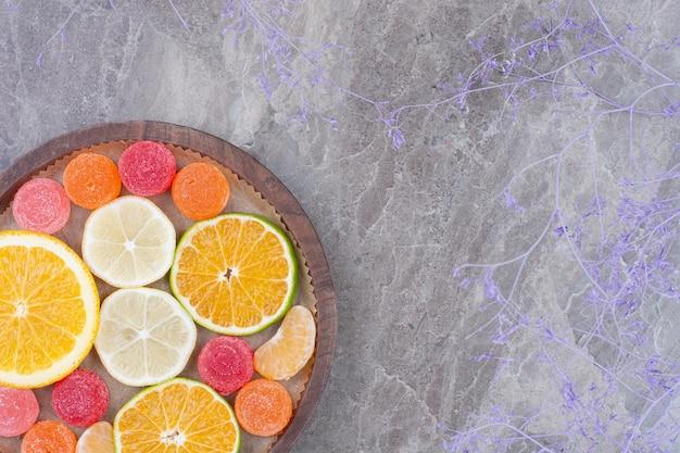 오렌지, 귤, 나무 접시에 사탕의 조각.