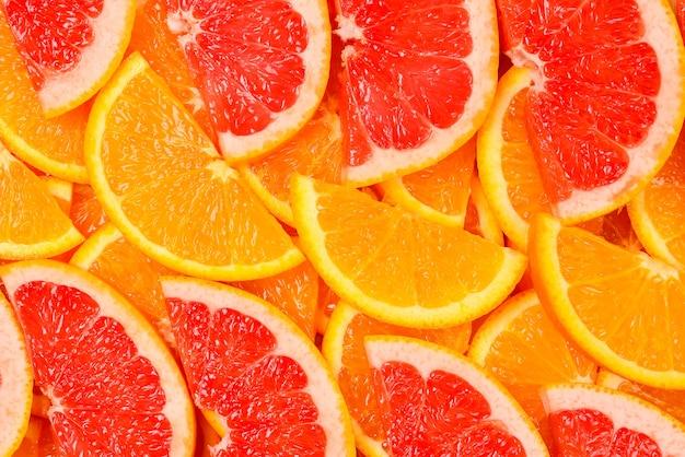 背景としてオレンジとグレープフルーツのスライス。