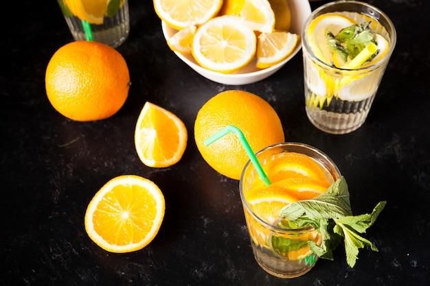 짙은 빈티지 나무 배경에 있는 해독수에 오렌지와 레몬 조각