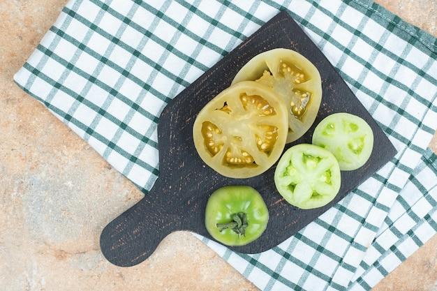 Ломтики маринованных помидоров и свежих зеленых помидоров на темной доске
