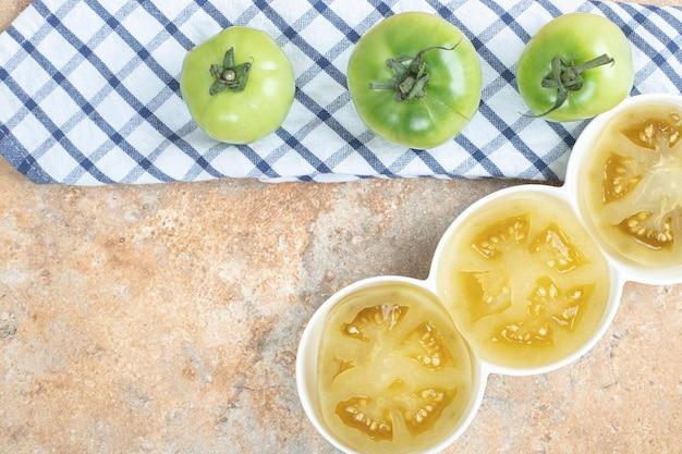 Ломтики маринованных помидоров и свежих зеленых помидоров на мраморной поверхности.