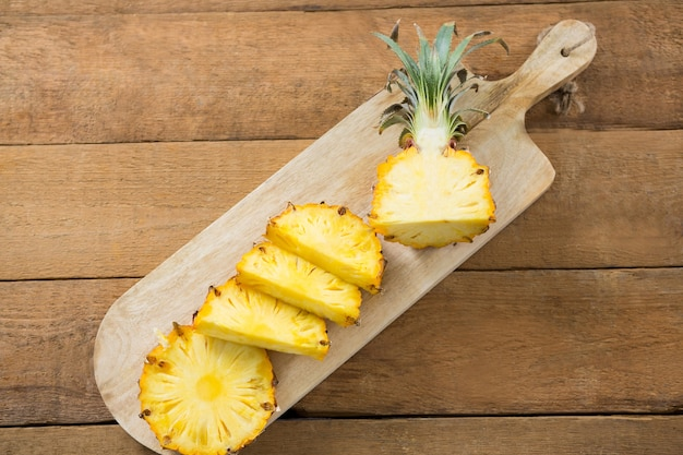 木製のテーブルのまな板にパイナップルのスライス