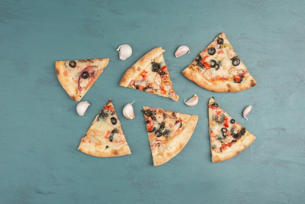 Кусочки пиццы и чеснока на синей поверхности.