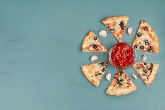 青いテーブルの上にピザと赤唐辛子のピクルスボウルのスライス。