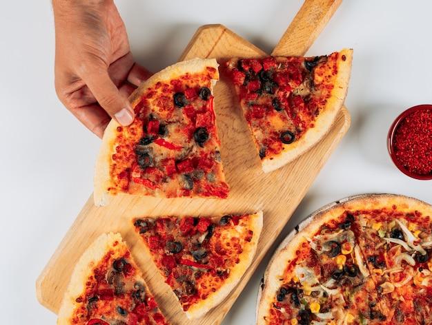 白い背景に、ハイアングルでピザボードにスパイスとピザのスライス。