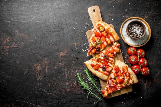향신료, 토마토, 로즈마리와 피자 조각. 어두운 소박한 배경에