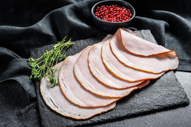 タイムと豚肉のハムのスライス。有機肉。黒の背景。上面図。