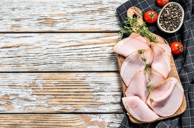 まな板の上に豚のパストラミのスライス。有機肉。白色の背景。上面図。スペースをコピーします。