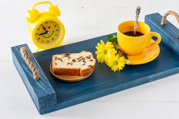 쟁반에 건포도와 커피 한 잔을 곁들인 파운드 케이크 조각. 아침 맛있는 아침 식사.
