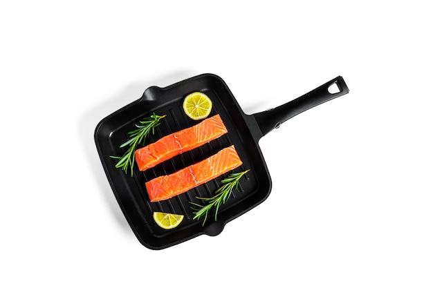 Кусочки сырого лосося на сковороде-гриль с лимоном и розмарином, изолированными на белом.