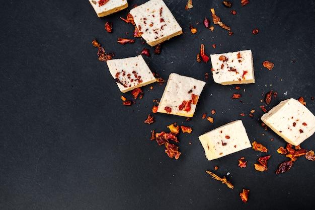 生豆腐のスライス黒地に生豆腐のスライス、パプリカをまぶした。